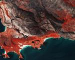 Sentinel-2 image shows burnscars near Cape Town, South Africa. The false-colour image shows burnt areas in dark greys and browns, and areas covered with vegetation in red.Image: ESA/ CC BY-SA 3.0 IGO.